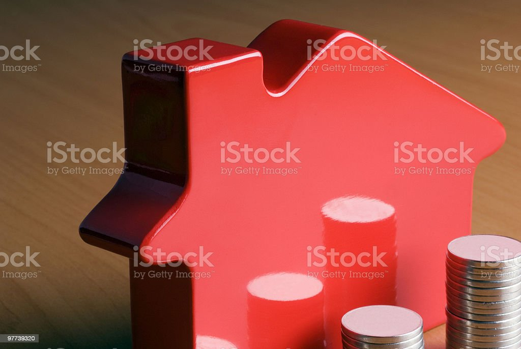 Stacked coins in front of toy house royalty-free stock photo