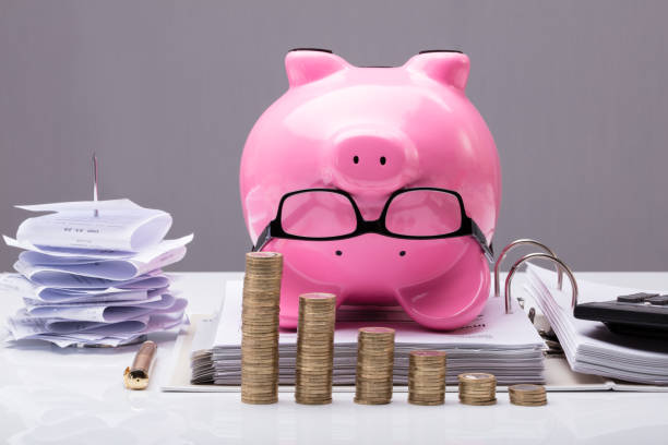 Stacked Coins In Front Of Upside Down Piggy Bank Close-up Of Stacked Coins In Front Of Upside Down Piggy Bank On Documents In Office 40 kilometre stock pictures, royalty-free photos & images
