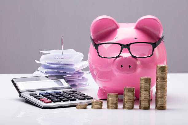 Stacked Coins With Piggy Bank And Calculator Close-up Of Stacked Coins With Piggy Bank And Calculator On Desk 40 kilometre stock pictures, royalty-free photos & images