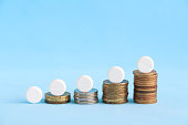 istock stacked coins with white pills on the top 1212490034