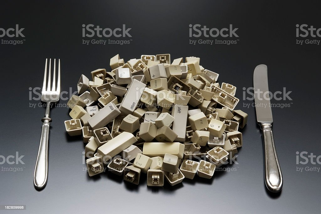 Stacked computer keyboard keys with silverware on office desk royalty-free stock photo