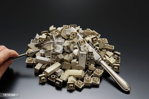 istock Stacked computer keyboard keys with silverware on office desk 182909617