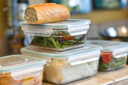 Containers of leftover food stacked on kitchen counrter