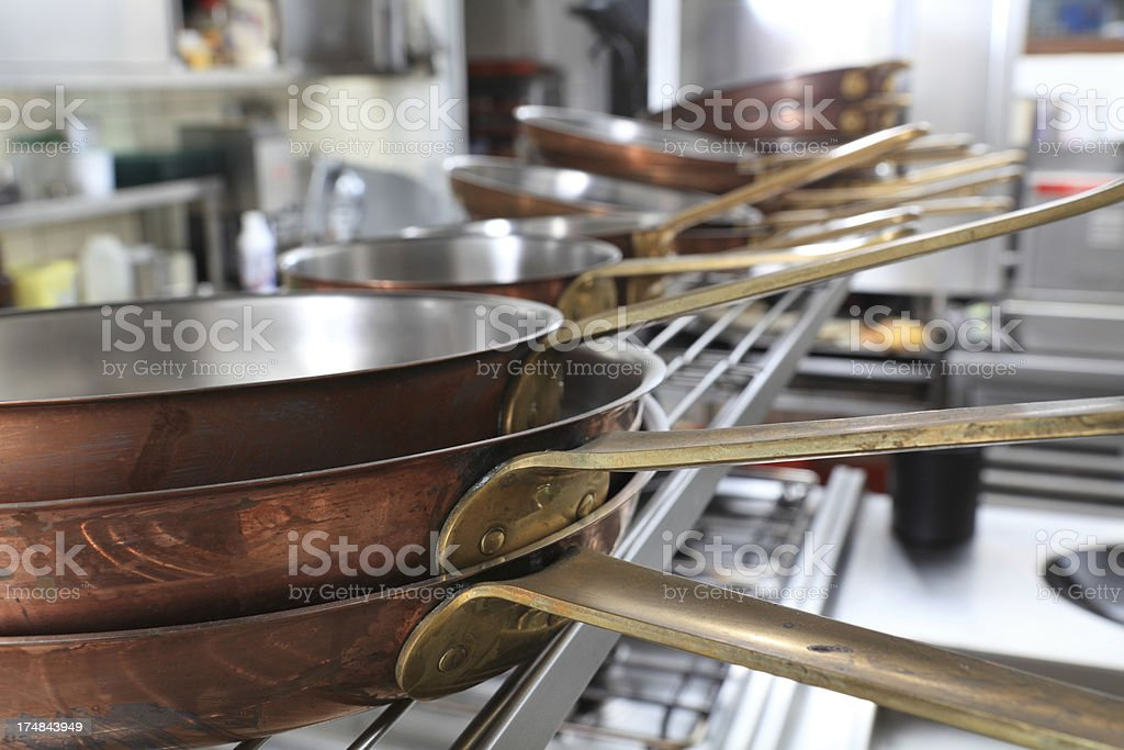 stacked copper fryingpans in a professional kitchen stock photo