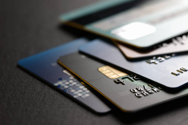 Stacked credit cards stack of multicolored credit cards on black background banking stock pictures, royalty-free photos & images