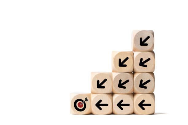 Stapelte Würfel mit einem Zielsymbol und Pfeilen, die auf dieses Ziel zeigen, symbolisieren, ein Team zu einem gemeinsamen Ziel zu organisieren – Foto