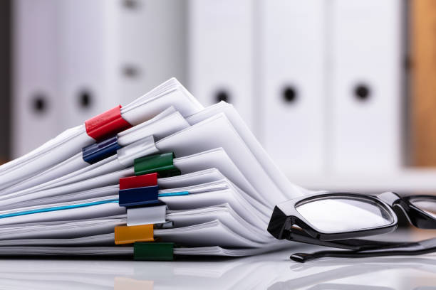Stacked Documents And Eyeglasses Stacked Documents With Colorful Paperclips And Eyeglasses document stock pictures, royalty-free photos & images