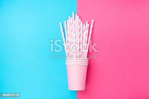 istock Stacked Drinking Paper Cups with Striped Straws on Duo Tone Mint Blue Pink Background. Flat Lay. Birthday Party Celebration Kids Fun. Greeting Card Poster Template. Copy Space 946820178