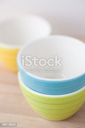 Studio photo of stacked group of pastel colored ceramic mixing bowls on wood surface. Very selective focus in front of bowls.