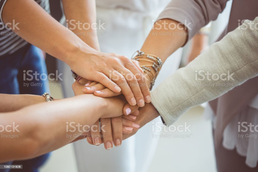 Stacked hands showing unity and trust Group of women making a pile of hands during training programme. Close up of female hands stacked together showing unity and trust. A Helping Hand Stock Photo