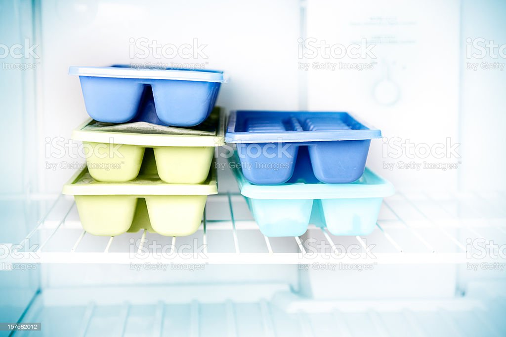 Stacked ice cube trays in a freezer stock photo