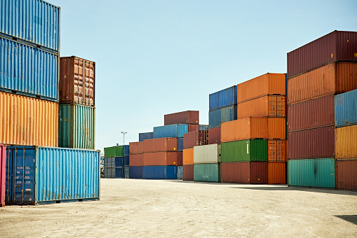 Multi-colored shipping containers stacked outdoors and awaiting transport from terminal to next destination.