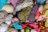 Stacked knitting yarns, a pair of knitting needles and hand-knitted baby shoe, top view