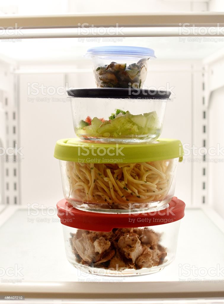 Stacked Leftovers in Fridge This image is of stacked food storage containers in the fridge filled with leftovers of diced chicken, spaghetti, diced cucumbers and diced mushroom.  Each food storage container has a different color lid.  2015 Stock Photo