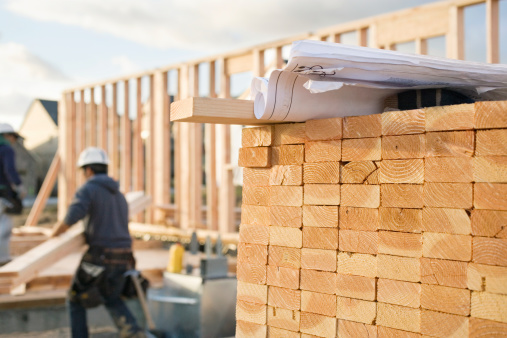 A closeup of stacks of 2x4 boards at a construction site, with a roll of blueprints sitting on top.  Two construction workers and a building frame can be seen in the background. Horizontal shot.