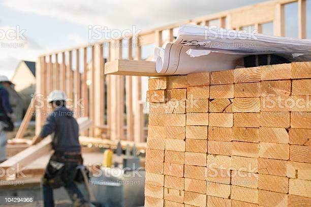 Stacked Lumber And Blueprints At A Construction Site Stockfoto en meer beelden van Arbeider