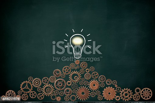 istock Stacked metal gears and illuminated light bulb drawn on blackboard 846211876