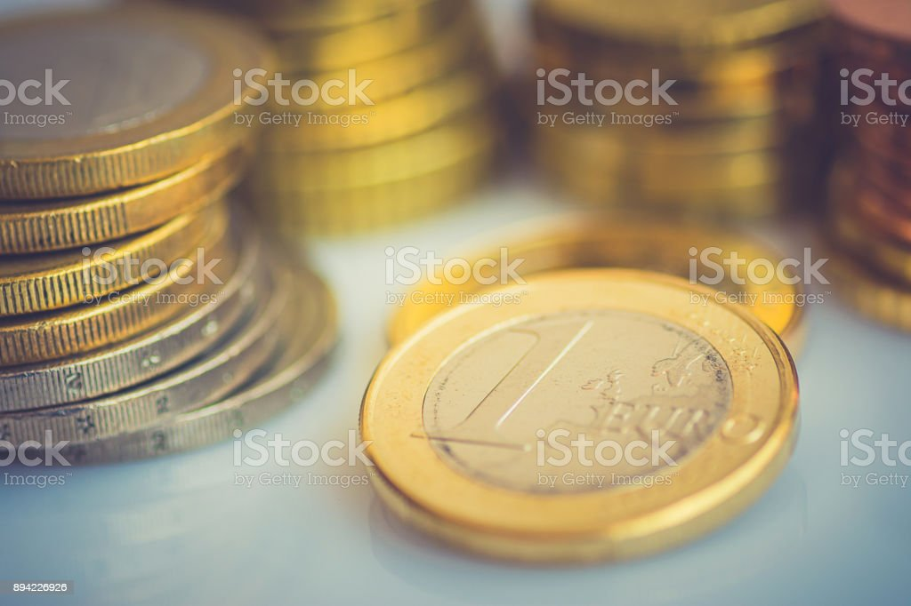 Stacked New Shiny White and Golden Euro Coins of Different Value on Desktop Finances Investment Stock Savings Concept Toned Vintage stock photo