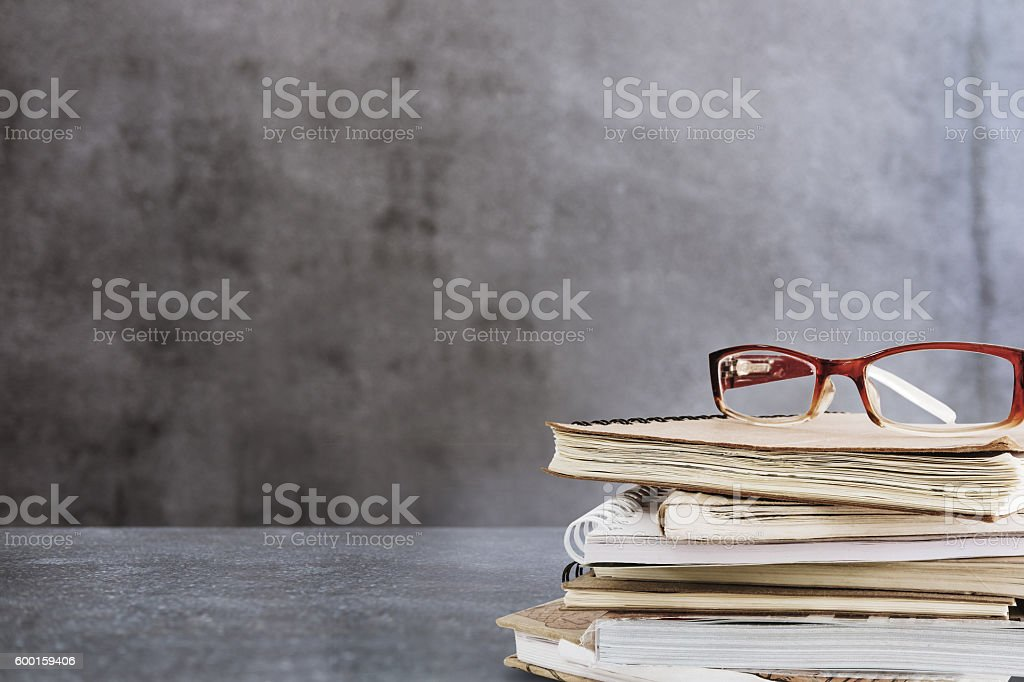Stacked of textbook with eye glasses, on concrete desk stock photo