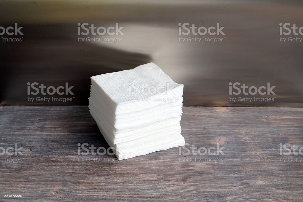 Stacked paper napkins on wooden table. Concept of cleanliness. stock photo