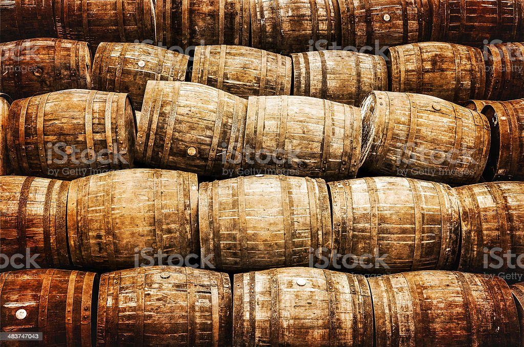 Stacked pile of old vintage whisky and wine wooden barrels stock photo