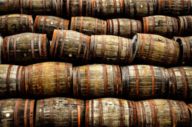Stacked pile of old whisky and wine wooden barrels stock photo