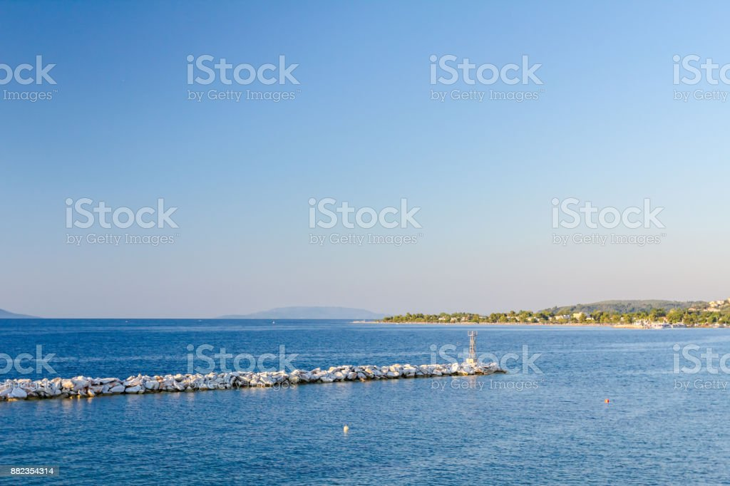 Stacked pile of stones as huge artificial reef along seashore stock photo