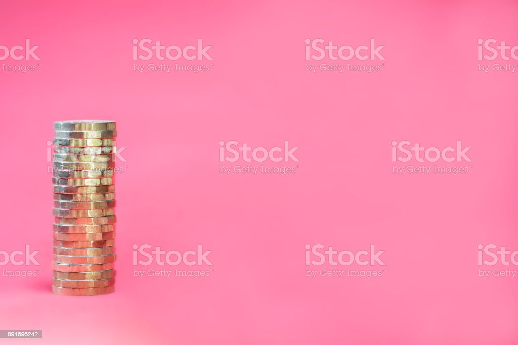 Stacked Pound Coins on a Pink Background stock photo