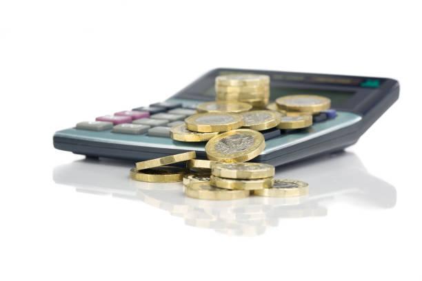 gestapelte pfund-münzen mit rechner - weißen reflektierenden hintergrund - wirtschaftsrecht stock-fotos und bilder