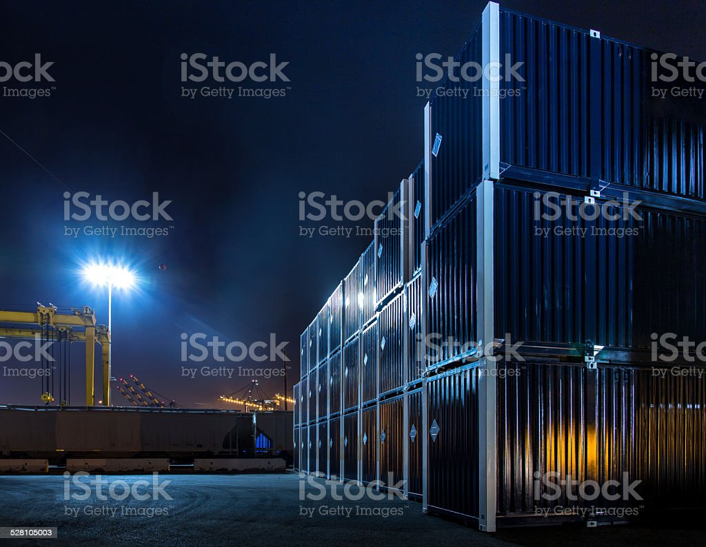 Stacked Shipping Containers in Dockyard at Night stock photo