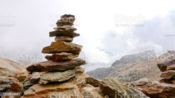 Photo of Stacked stone tower in the middle of a foggy, cloudy, rust-brown, Mars-like stone desert on Mount Punta Taviela at an altitude of about 3000m in the Val di Sole ski area, Dolomites, Italy.