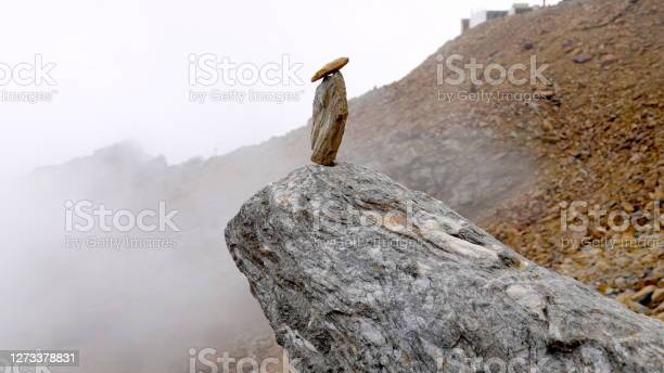 Photo of Stacked stones in the middle of the misty, Mars-like stone desert on the punta Taviela mountain at an altitude of about 3000m in the Ski Resort Val di Sole, Dolomites, Italy.