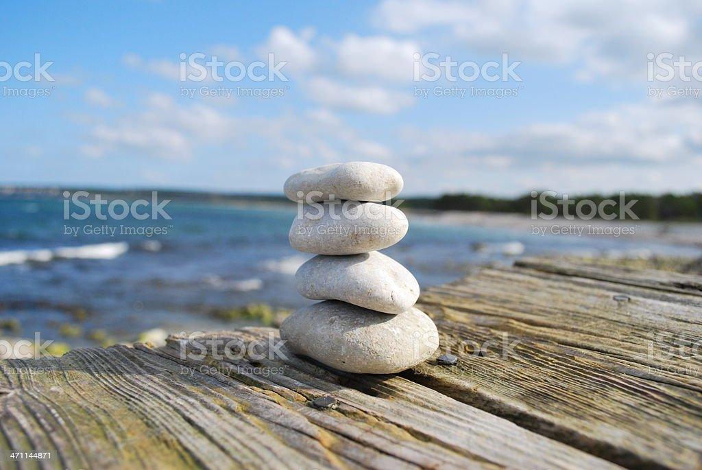Stacked stones on old wooden bench royalty-free stock photo