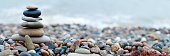 Panoramic shot of pebble stones on the sea beach
