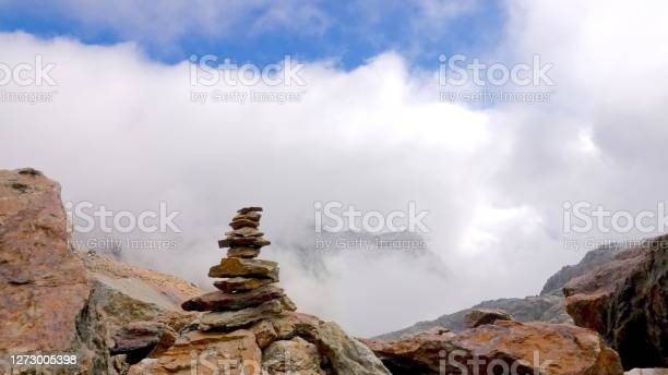 Photo of Stacked tower of stones in the middle of a cloud, rust-brown, Mars-like stone desert on the mountain Punta Taviela at about 3000m altitude in the ski resort Val di Sole, Dolomites, Italy.