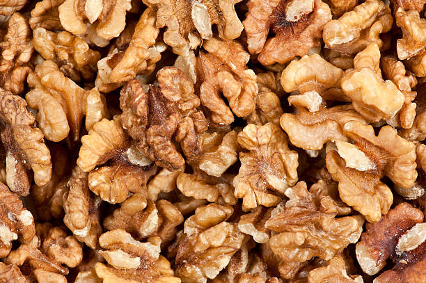 stacked unshelled walnuts background - walnut stock photos and pictures