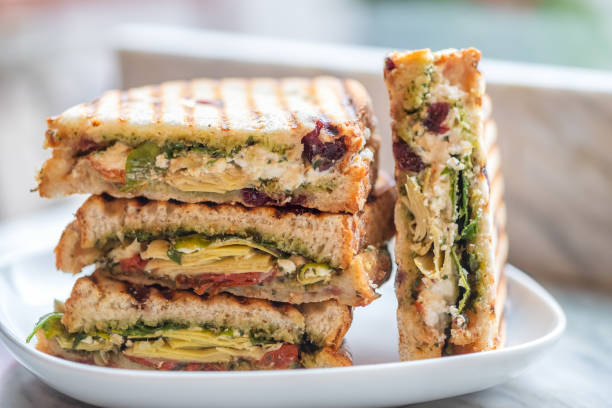 stacked vegetarian sandwiches of arugula, artichoke, sun dried tomato, pesto - panino ripieno foto e immagini stock