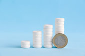 istock Stacked white pills and one euro coin 1212489989