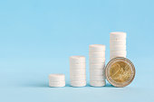 istock Stacked white pills and two euro coin 1212489945