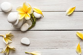 Stacked white stones on white background with yellow frangipani flower - flat lay arrangement lifestyle and alternative health concept image with copy space for text.