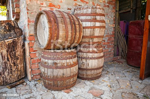 Four vintage wooden barrels are against a brick wall.