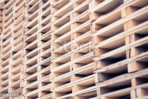 Stacks of wooden pallets in outdoor warehouse.