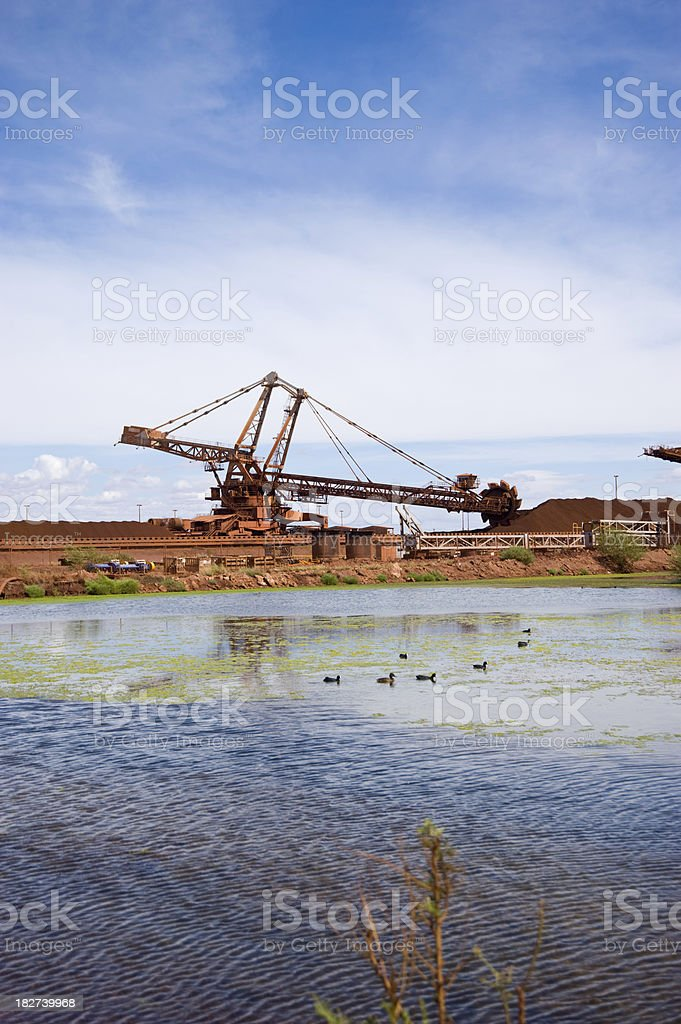 Stacker Reclaimer and Stockpile Mine Site with ducks on lake stock photo