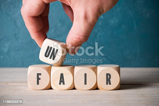 Unidentifiable person stacking blocks with black letters on side to spell unfair in front of scuffed blue wall