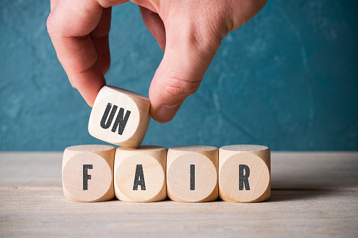 istock Stacking blocks with letters to spell unfair 1158033379