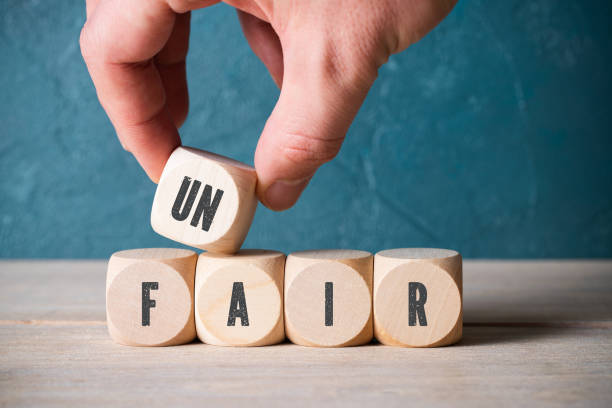 Stacking blocks with letters to spell unfair Unidentifiable person stacking blocks with black letters on side to spell unfair in front of scuffed blue wall discriminatory stock pictures, royalty-free photos & images