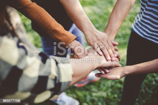 istock Stacking hands of young teen student, teamwork, togetherness and cooperation concept 985577158