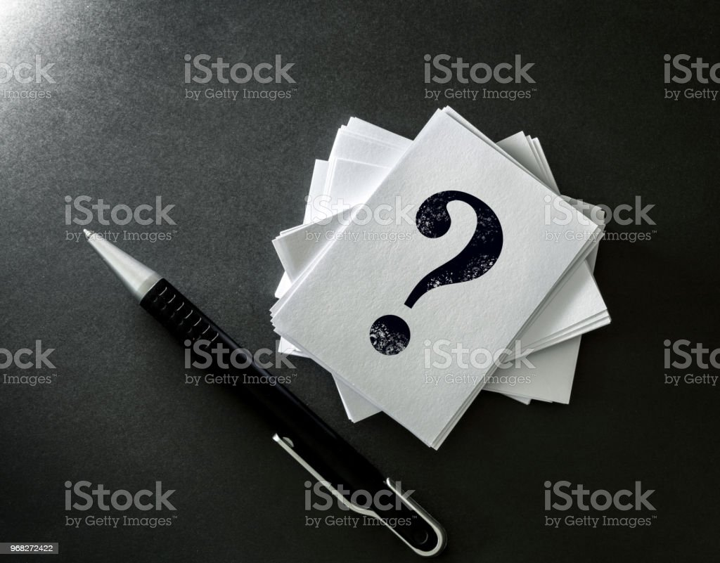 Stacking of a white business card with written question mark symbol stacking of a white business card with written question mark symbol on black background questions reheart Images