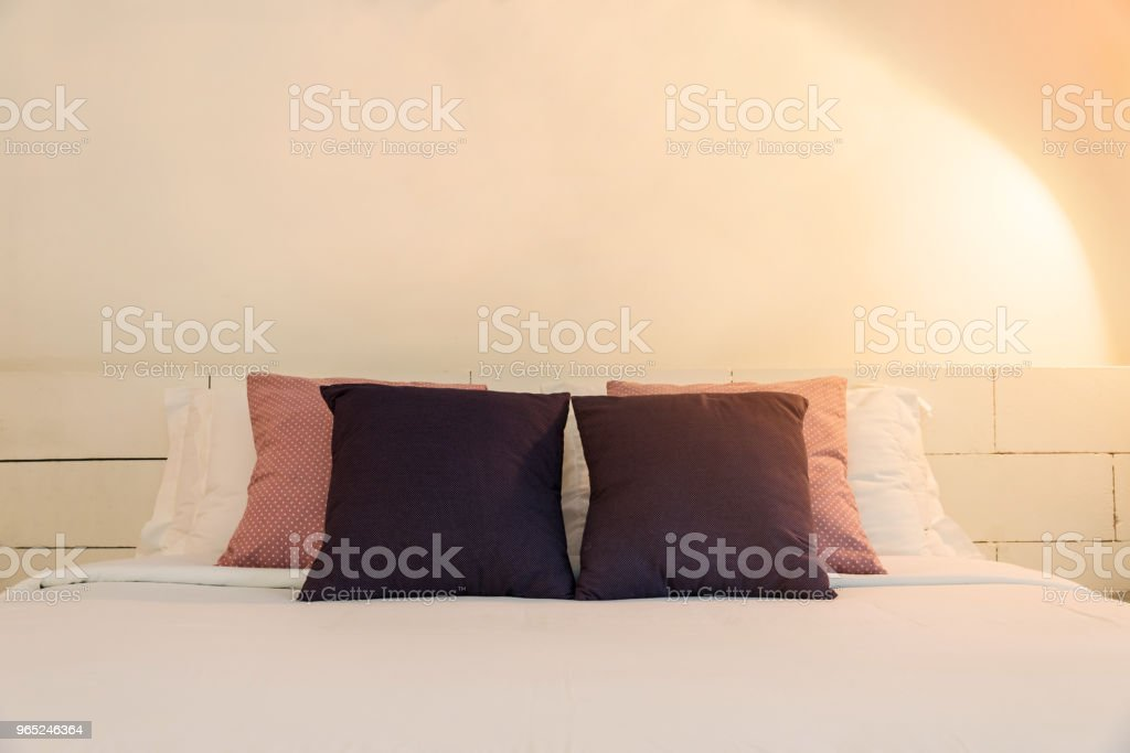 stacking of backrest pillow and white pillow on bed and white brick wall, interior modern bedroom zbiór zdjęć royalty-free