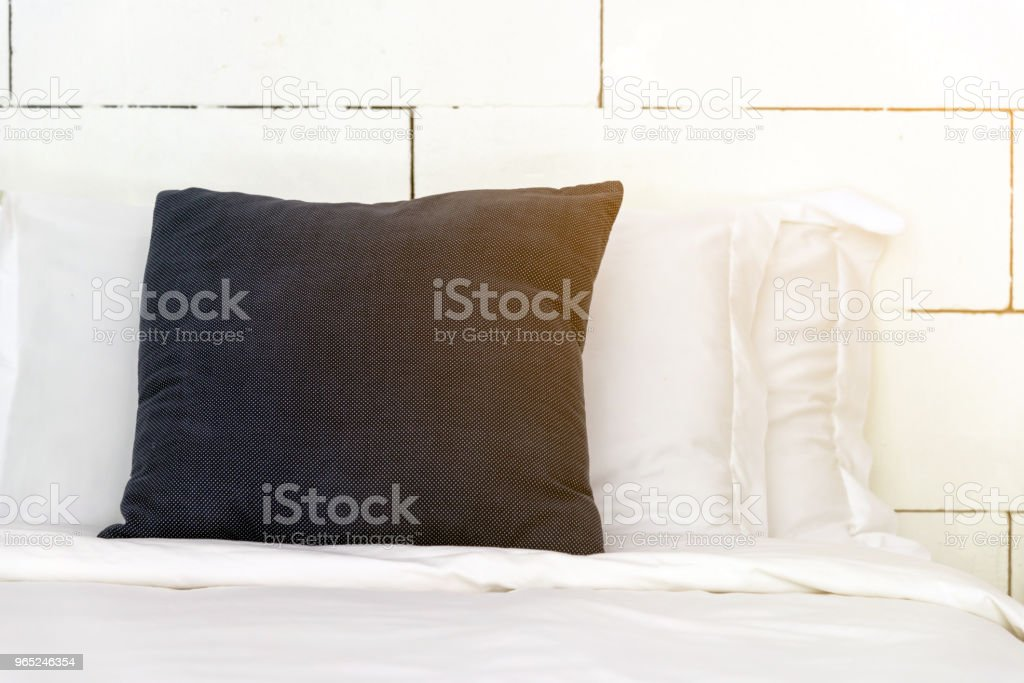 stacking of blue backrest pillow and white pillow on bed and white brick wall, interior modern bedroom royalty-free stock photo